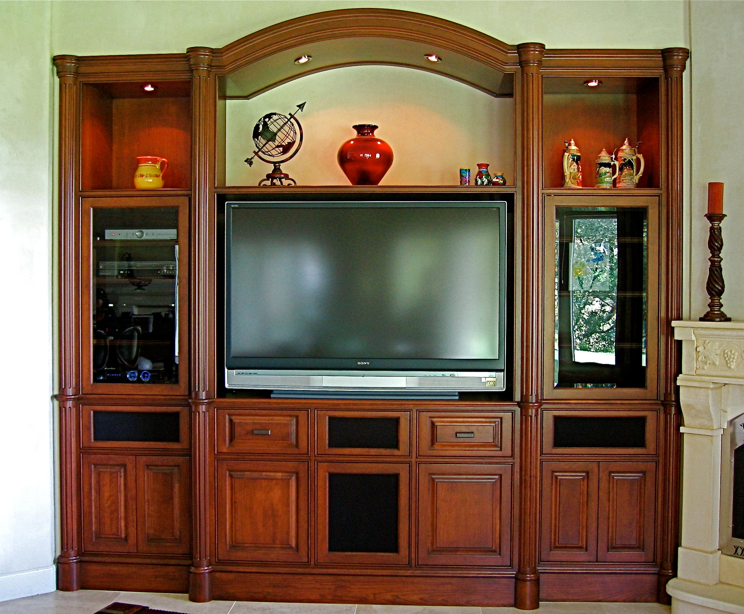 Custom Cherry built in media center designed and handcrafted by Philip Snyder of PS Woodworking features a graceful arch, round fluted columns, plinths and capitals, speakers behind cloth panels, custom one of a kind moldings and is the focal point of the great room.