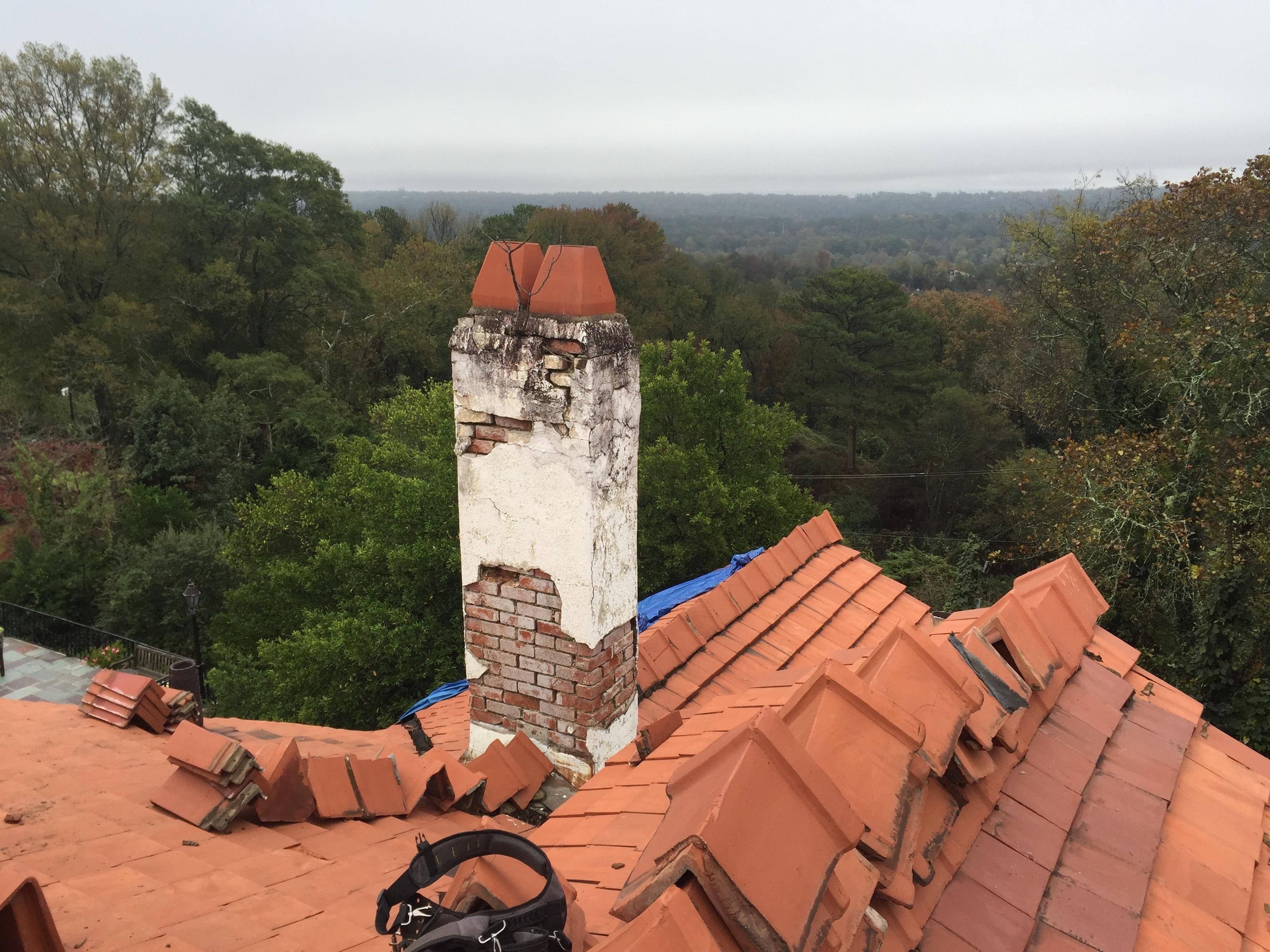 Capstone Roofing removing an old clay roof to repair chimney and install new clay tile in Birmingham, Alabama.
