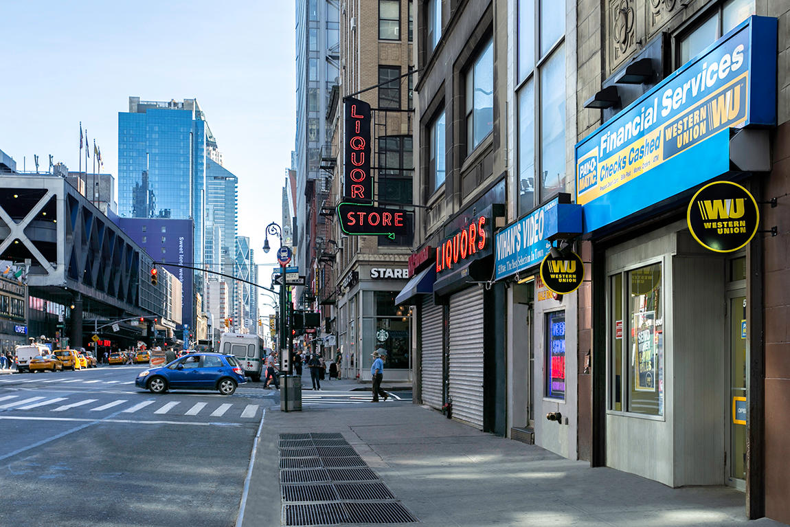 Exterior view from sidewalk of PAYOMATIC store located at 590 Eight Ave New York, NY 10018