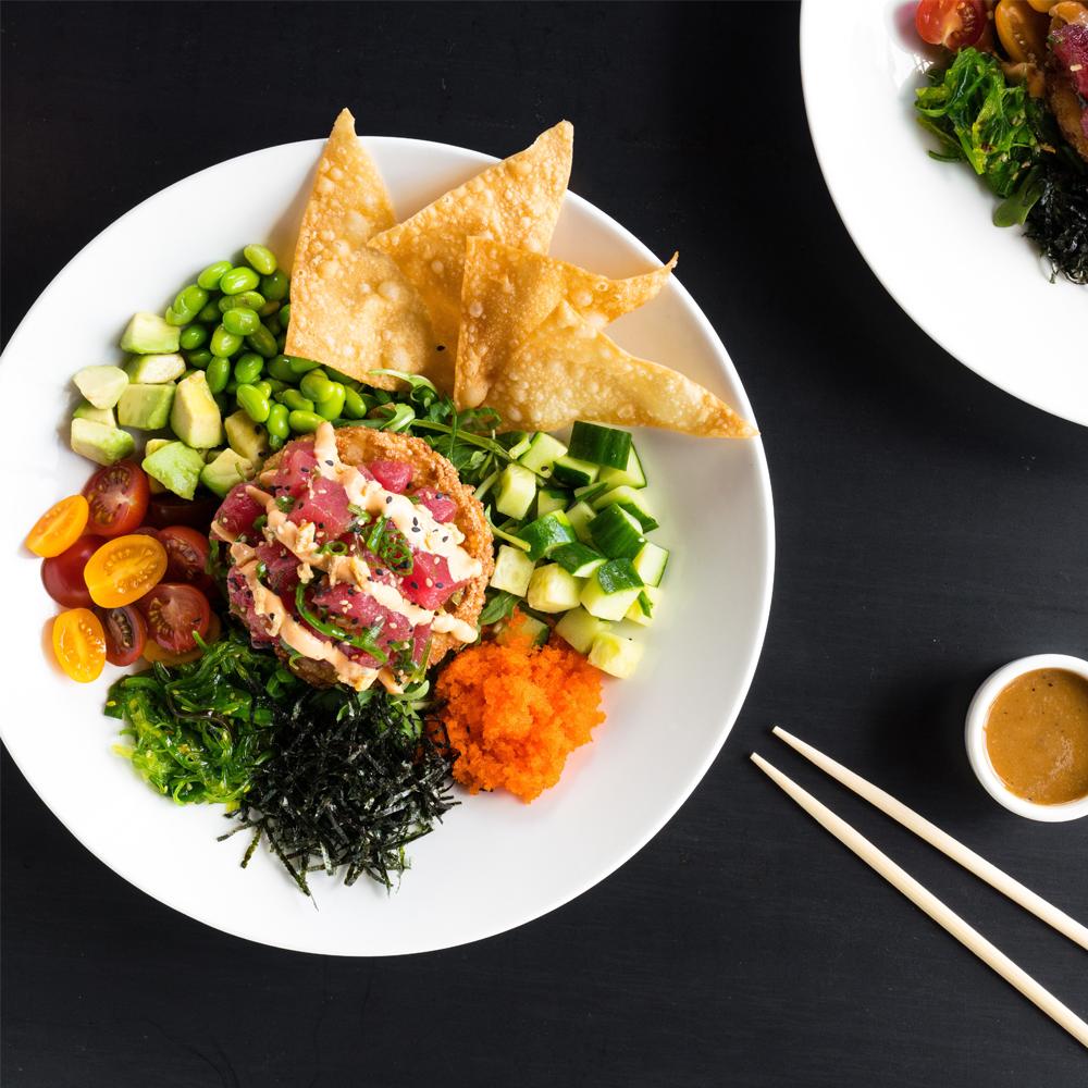 Poke Salad - raw ahi, arugula, avocado, cucumbers, seaweed salad, baby tomatoes, edamame, crispy wonton, masago, nori, soy vinaigrette & sriracha aioli.