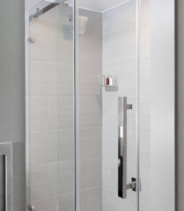 Sleek bathrooms offer a back-lit mirror and glass-enclosed shower.