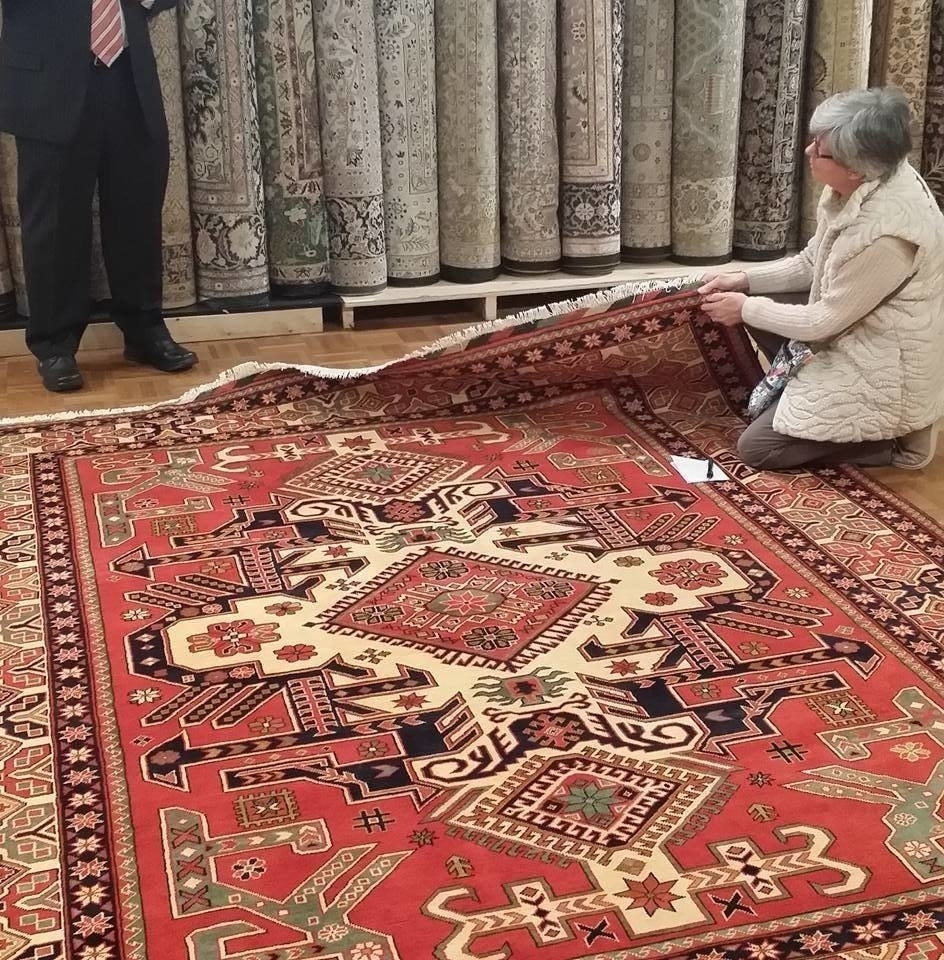 Tapis d'Orient Bashir à Montréal: A customer, with a notebook in hand, carefully examines a Caucasian carpet she recently dropped off at our Montreal Store for repairs. The verdict: A+